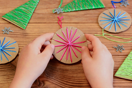 Child is holding a Christmas ball in his hands. Child is showing a Christmas ball decor. Simple recycled crafts and activities for kids. Christmas decor set on a wooden table Stock Photo