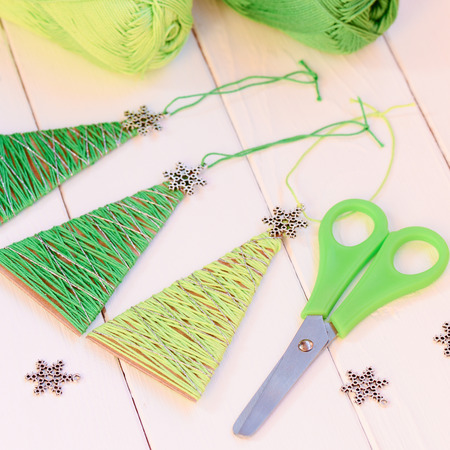 Original Christmas trees ornaments, scissors, metal snowflakes, cotton yarn on a wooden table. Simple and adorable Christmas trees ornaments from recycled materials Foto de archivo