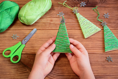 Kid is holding a Christmas tree decoration in his hands. Kid is showing a Christmas tree decoration. Merry Christmas tree project for kids. Scissors, green cotton yarn on a wooden table Banco de Imagens - 91732829
