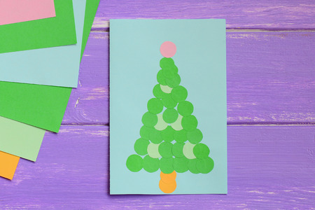 Paper greeting card with green Christmas tree, colored paper sheets on a purple wooden table. Simple Christmas tree card gift idea for kids. Top view. Closeup
