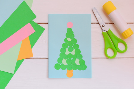 Paper greeting card with Christmas tree, colored paper sheets, scissors, glue stick on a wooden table. Easy paper. Top view