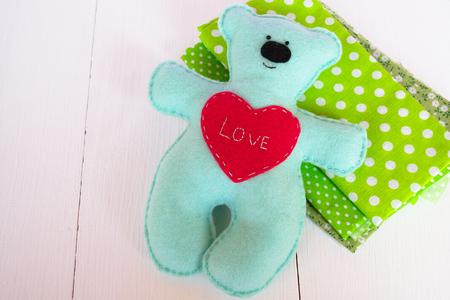 Handmade felt bear - felt on wooden background, hand-stitched toy, a craft out of felt