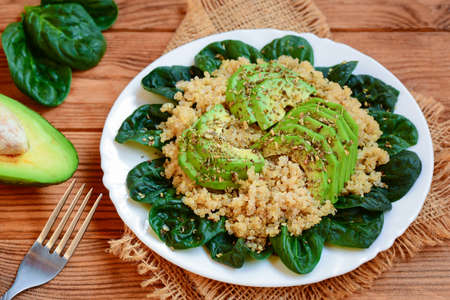Avocado quinoa salad. Easy quinoa salad with fresh spinach leaves and avocado slices on a served plate. Brown wooden background. Rustic style. Closeup. Quinoa salad with avocado. Quinoa avocado salad