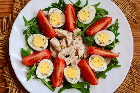 Chicken breast, tomatoes, quail eggs and arugula salad. Healthy and tasty salad for lunch or dinner. Top view. Chicken vegetable salad. Chicken salad with mixed vegetables 版權商用圖片