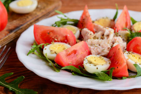 Chicken fillet, tomatoes, quail eggs and arugula salad. Healthy and satisfying salad for lunch or dinner. Closeup. Chicken vegetable salad. Chicken salad with mixed vegetables