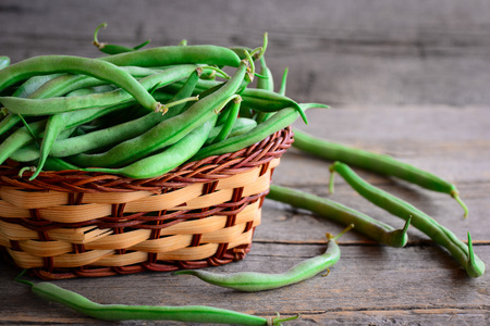 Fresh raw green beans in a brown basket and on a vintage wooden table. Young beans pods photo. Green string beans crop