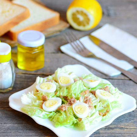 Tuna cabbage salad. Simple salad with chinese cabbage, quail eggs and canned tuna fish on a plate. Fork, knife, olive oil bottle, salt shaker, lemon, bread pieces on rustic wooden table. Closeup Stock Photo