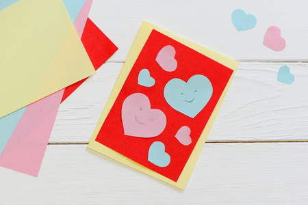 Valentines day card with pink and blue hearts, scissors, glue stick, colored paper sheets on a wooden background with copy space. Simple Valentines day paper crafts. Paper art design. Top view Stock Photo