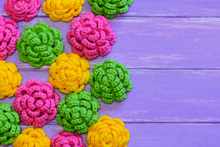 Crocheted roses. Yellow, pink and green crocheted roses. Colorful floral decorations on a wooden background with copy space for text. Top view