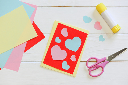 Valentines day or Mothers day card with pink and blue hearts, scissors, glue stick, colored paper sheets on a wooden table. Easy art and craft with paper for kids. Top view