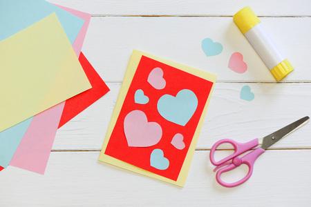Valentinstag- oder Muttertageskarte mit den rosa und blauen Herzen, Scheren, Klebestift, Blätter des farbigen Papiers auf einem Holztisch. Einfaches Basteln mit Papier für Kinder. Ansicht von oben