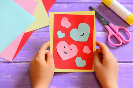 Child is holding a Valentines greeting card in his hands. Child is showing a Valentines greeting card. Simple paper crafts for children concept. Closeup