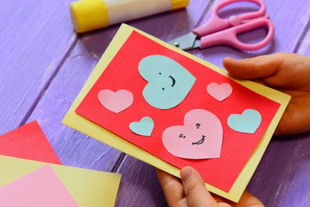 Criança está segurando um cartão de dia dos namorados em suas mãos. Criança está mostrando um cartão de saudação. Feliz dia dos namorados cartão. Artesanato de papel fácil para o conceito de crianças. Fechar-se