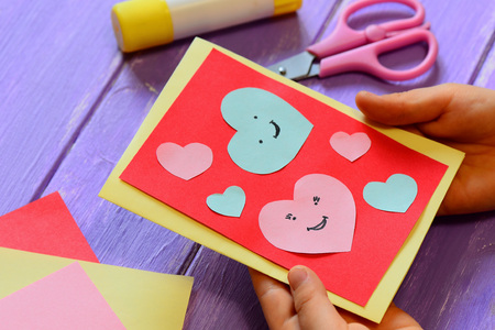 Child is holding a Valentines card in his hands. Child is showing a greeting card. Happy Valentines Day card. Easy paper crafts for kids concept. Closeup