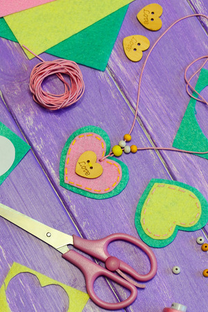 Felt heart necklace. Valentine's day necklace made of felt, beads and a wooden button. Craft supplies on a wooden table. Valentines day gift idea. Gift for mom. Simple children creativity idea