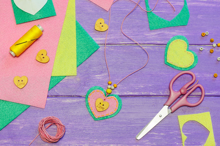 Simple felt heart pendant necklace. Valentines day pendant necklace made of felt, beads and wooden button with text love. Kids art workplace. Gift for mum. Fun creative art activity for preschoolers
