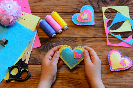Child holds a felt valentine in his hands. Child made valentines from felt. Valentines day crafts idea. Felt heart ornaments, scissors, thread, felt sheets on a wooden table. Sewing craft projects Stock Photo