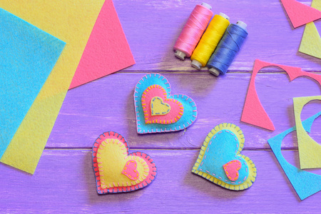 Valentines day decorations idea. Beautiful felt heart decorations, thread set, felt sheets and pieces on a wooden table. Creative Valentines gift idea. Easy sewing Valentines day gifts. Top view Stock Photo
