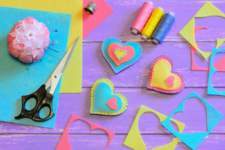 Valentines day decorations. Felt heart decorations, scissors, thread, pincushion, thimble, felt sheets and pieces on a wooden table. Valentines gift idea. Sewing homemade Valentines day gifts Stock Photo