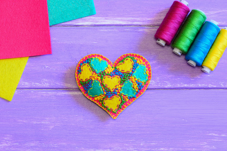 Embroidered heart ornament. Valentines Day heart ornament, thread set, colorful felt sheets on a wooden table. Embroidery motif. Top view. Closeup Stock Photo