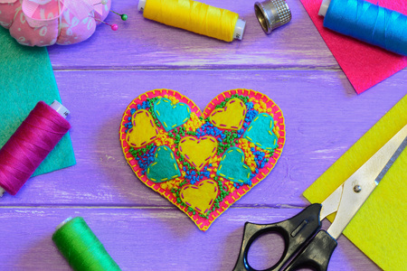 Embroidered Valentine heart ornament. Stuffed felt heart ornament, thread set, scissors, thimble, colorful felt on a purple wooden background. Sewing hobby idea. Top view Stock Photo