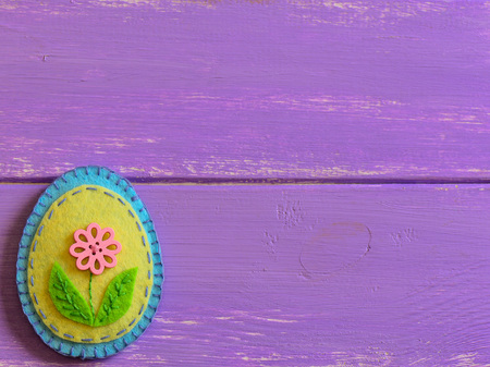 Felt Easter egg decoration with pink flower isolated on a wooden background with copy space.