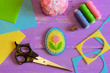 Cute handmade felt Easter egg, colored thread set, scissors, thimble, pin cushion, felt scrap and sheets on a purple wooden table. How to sew patchwork felt Easter egg. Top view