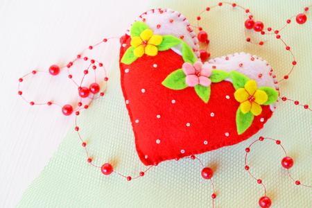 Handmade felt heart - symbol of Valentines Day, felt toy on white background. Valentines day homemade crafts. Valentines day crafts Stock Photo