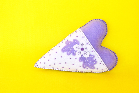 Hand-stitched felt heart - symbol of Valentines Day, handmade felt toy on yellow background, with place for text Stock Photo