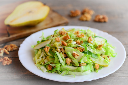 Home cabbage slaw with pear and walnuts. Healthy pear and cabbage slaw on a plate. Great food for getting vitamins. Closeup