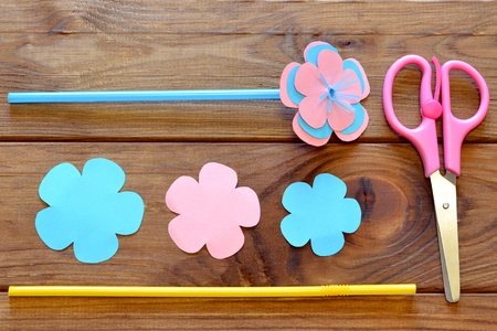 Paper flowers, scissors, straws - set for childrens art. Wooden table. Top view Stock Photo