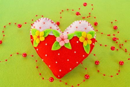 Handmade felt heart. Symbol of Valentines Day, felt toy on white background. Valentines day decor. Felt heart. Valentines day heart. Gift for Valentines day decor. Felt Heart ornament. Valentine decoration Stock Photo