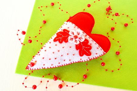 Handmade felt heart. Symbol of Valentines Day, felt toy on white background. Valentines day decor. Felt heart. Valentines day heart. Gift for Valentines day decoration. Felt Heart ornament. Valentine ornament crafts