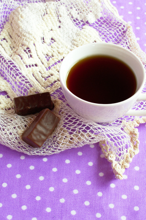 A cup of black coffee, 2 chocolate candies on a white and purple background, good morning Stock Photo