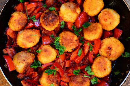Rice balls with vegetables. Fried rice balls with stewed red pepper, onions and tomatoes in a pan. Homemade veggie balls in vegetable sauce. Easy vegetarian recipe