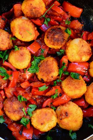 Fried rice balls with vegetables. Homemade fried rice balls with stewed red pepper, onions and tomatoes in a pan. Homemade veggie balls in vegetable sauce. Easy vegetarian recipe