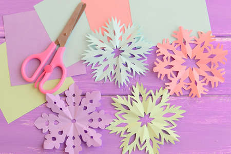 Pink, purple, blue, green paper cut snowflakes, stationery craft supplies on wood background. Merry Christmas paper snowflakes cutouts craft art. Winter diy projects for kids 版權商用圖片