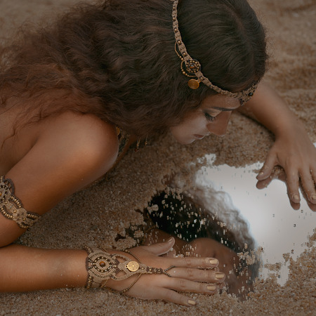 Beautiful girl in ethnic jewelry with mirror covered with sand