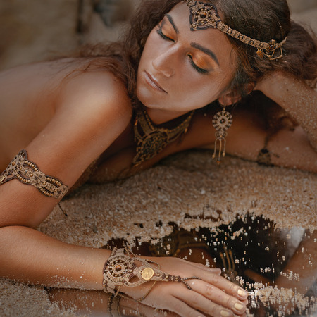 gypsy woman: Beautiful girl in ethnic jewelry with mirror covered with sand