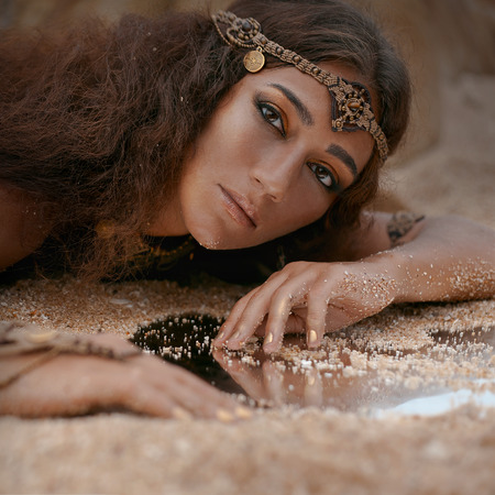squaw: Beautiful girl in ethnic jewelry with mirror covered with sand