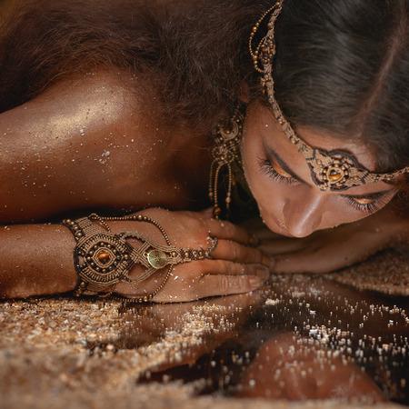 Krásná dívka v etnické šperky se zrcadlem pokrytá pískem