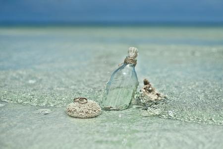 Dva snubní prsteny na korálovém kameni s skleněné láhve a mušlemi na tropické pláži v Thajsku.