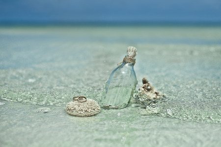 Two wedding rings on the coral stone with the glass bottle and sea shells on tropic beach in Thailand.