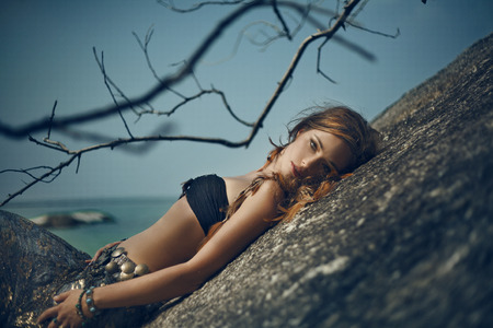 Tribal style girl on the stone rocks. Koh Phangan Thailand Reklamní fotografie