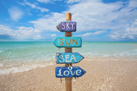 Blue signpost made of wood and bamboo on the tropical beach in Thailand. Space for text.