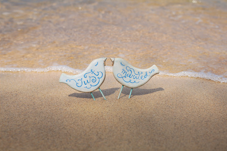 wooden handmade: Two blue wooden handmade toy birds decorated with the inscription Just Married with two wedding rings in their beaks on the beach in Thailand.