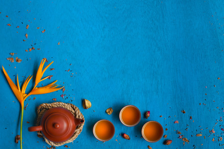teacup: Clay teapot, three teacups and yellow flower with the rope, shuck and rose buds on blue wooden background. Top view. Space for text. Horizontal. Stock Photo