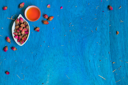 small plate: Teacup and small plate with rose buds on blue wooden background. Top view. Space for text.