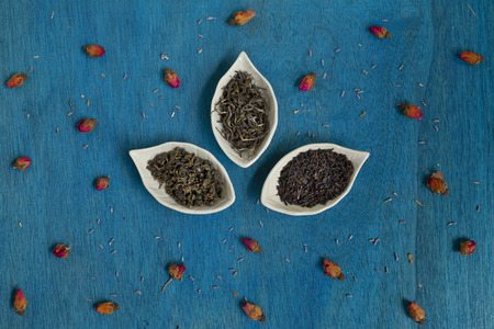 bourgeon: tea leaves on a plate with rose buds and lavender seeds on blue wooden table.