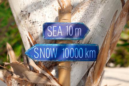 wooden handmade: Blue wooden handmade signpost with the inscription sea, snow on tropic beach. Stock Photo